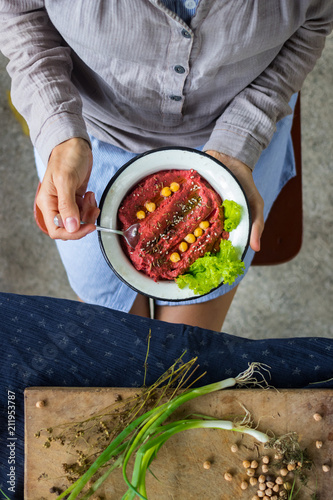 Foto op Canvas Kruidenierswinkel Woman hands holds spicy red beetroot Israeli chickpea hummus with herbs and covered with olive oil. Traditional mediterranean food used with vegetables. Vegan vegetarian healthy food.