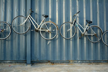 White Bicycles Hanging On Gray...