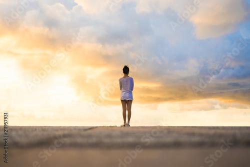 Fototapeta Woman looking at beautiful dramatic cloudy sky during sunset. obraz na płótnie