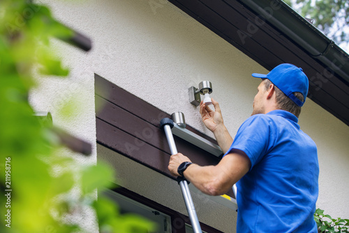 Leinwand Poster electrician standing on ladder and change the light bulb in house facade lamp