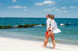 Happy couple walking on the beach, romantic travel honeymoon vacation.
