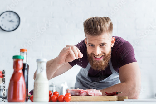 Fotografie, Obraz  handsome bearded man in apron cooking delicious steak and smiling at camera