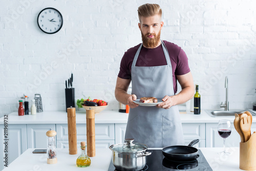 Fotografering  handsome bearded young man in apron holding delicious beef steak on plate and lo