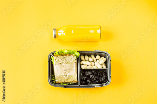 Foto op Aluminium Assortiment Lunchbox with food - sandwich, nuts and berries - next to a bottle of orange juice on a yellow background. Top view, flat lay,