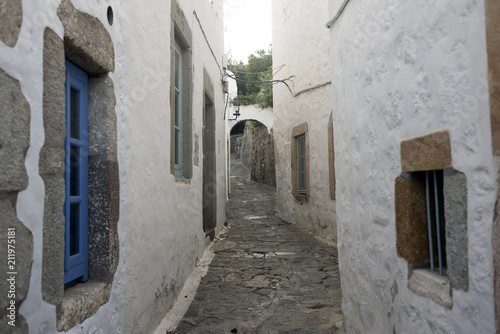 Poster Smal steegje A view of a narrow street with arch and wooden windows and doors with white wall stone architecture of the island Patmos, Greece