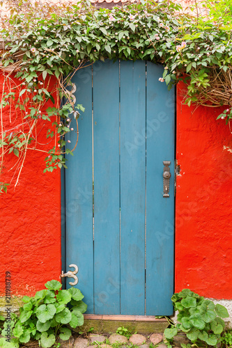 Photo sur Toile Jaune picture of a picturesque old wooden door in a red wall