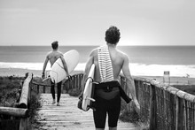 Two Surfers Running With Surfboards On The Beach. Men Walking Along The Wooden Path To The Ocean To Surf. Black And White Image
