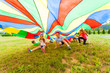 canvas print picture Smiling boy and girl under colorful parachute