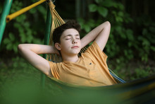 Teenager Boy Resting Sleep In Hammock On Summer Green Garden Background