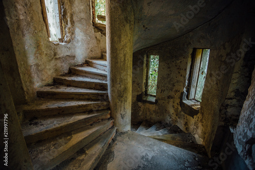 Old spiral staircase in tower of abandoned mansion