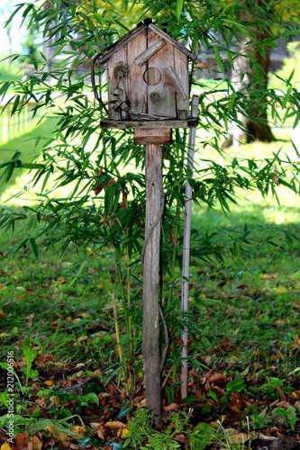 Fotografia, Obraz  Old aged vintage wooden bird house situated on top of wooden spike and supported