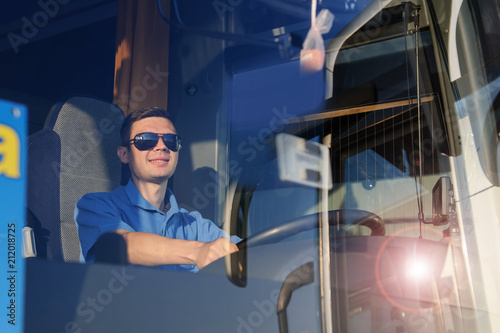 Young man at the wheel is looking away from the bus
