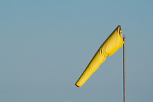A Brightly Coloured Yellow Windsock Gently Blows In The Morning Breeze Isolated Against A Clear Blue Sky Background.