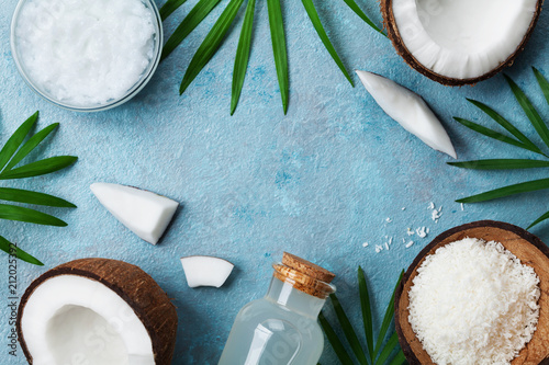 Blue background with set of organic coconut products for spa treatment, cosmetic or food ingredients. Oil, water and shavings top view. Flat lay.