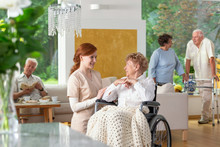 Seniors In A Luxury Living Room Of A Private Retirement Home. Tender Caregiver By An Elderly Lady In A Wheelchair In The Foreground.