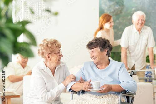 Staande foto Wanddecoratie met eigen foto Front view of two happy geriatric women talking and holding hands in a private luxury day care center. Other seniors in the blurred background.