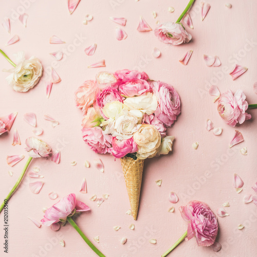 Flat-lay of waffle sweet cone with pink and white buttercup flowers over pastel light pink background, top view, square crop. Spring or summer mood concept