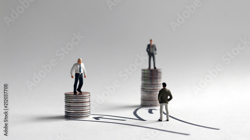 Fotografía  Two miniature men standing on a stack of coins of different heights and a miniature man standing in front of two different paths