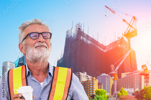 Photo  senior engineer with background development of city with under construction cran
