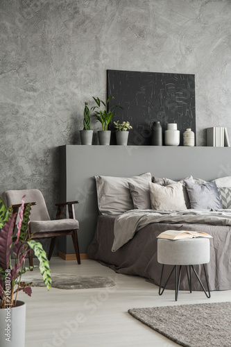 Earth colors bedroom interior with a big bed, an armchair, a ...
