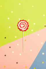 Red and white party lollipop on colored background