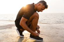 Photo Of Handsome Caucasian Man 30s In Tracksuit And Sneakers Squatting On Pier At Seaside, And Tying His Shoes