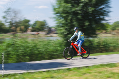 Deurstickers Fietsen A cyclist in a helmet rides a bicycle path, motion blur