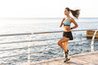 Photo of beautiful athletic sportswoman 20s in sportswear running along boardwalk near seaside in morning, with bluetooth earbud