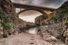 Italia, Luglio 2018 - Alba Al Ponte Ciolo Tra Santa Maria Di Leuca E Otranto. Si Nota Il Ponte Illuminato Dal Sole E La Piccola Spiaggia Deserta