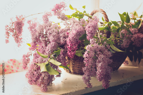 Fotobehang Lilac fresh blooming branches of lilac in a vintage wicker basket on the table home decor