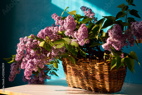 Staande foto Lilac fresh blooming branches of lilac in a vintage wicker basket on the table home decor