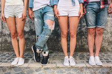 A Picture Of Teens' Legs. Three Of Them Are Standing Straight While Man In Jeans Is Holding Left Leg Over Right One. Girls Wear Shorts And One Boy As Well. They Are Standing On Grey Background.