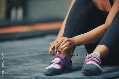 Fotografiet  Crop sportive female putting on sneakers sitting on mat in gym on blur backgroun