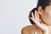 Crop Female With Dark Hair In Ponytail Touching Ear With Help Of Fingers And With Tenderness On Grey Background