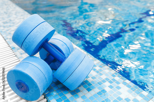 Fotografie, Obraz  dumbbells equipment for aqua aerobics sport near swimming pool