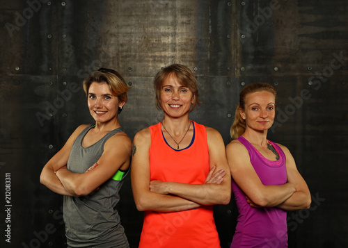 Portrait of three young athletic women in gym Wallpaper Mural
