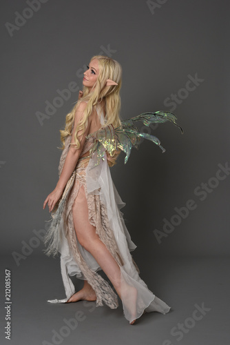 Valokuva full length portrait blonde girl waring fairy costume, standing pose with back to the camera
