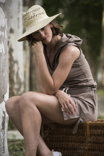Deurstickers Lovely model is sitting on a wicker trunk, sycamore tree on background.