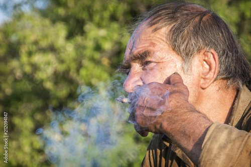 In summer, a drunkard stands in the garden and holds a cigarette in his hand Wallpaper Mural