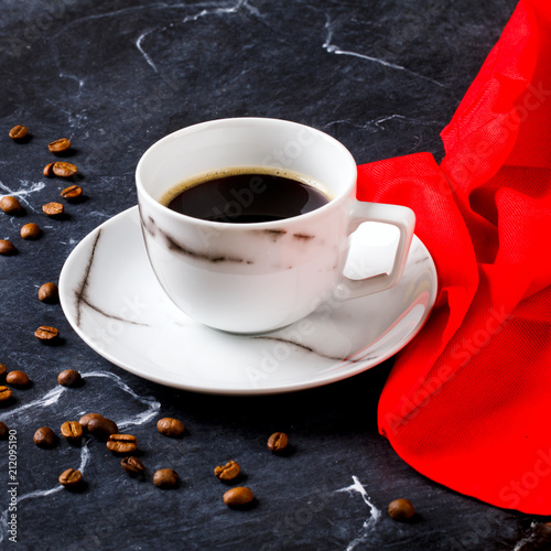 Foto op Aluminium Cafe Coffee cup on a dark marble background with a red napkin. Black espresso