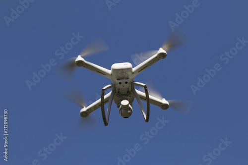 Tuinposter Helicopter quadcopter, drone quad copter with high resolution digital camera hovering in the blue sky