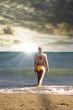 Hübsche, junge Frau geht zum Baden ins Meer