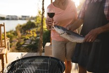 Senior Couple Holding Fish And Glass Of Wine In The Backyard