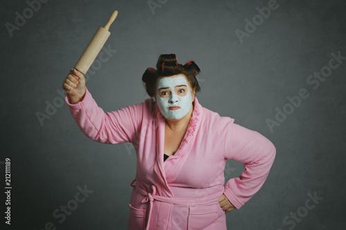 Fotografía  femme ronde et drôle avec bigoudis frappant avec un rouleau à pâtisserie