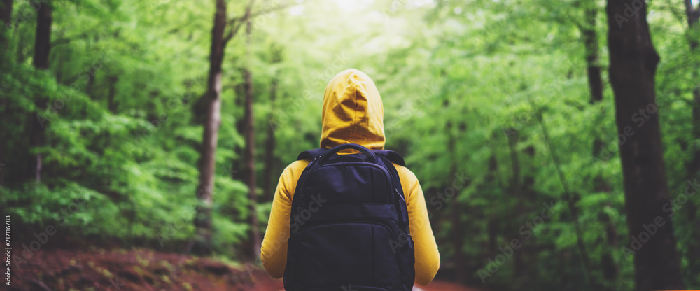 Fototapety, obrazy: tourist traveler with backpack standing into road at summer green forest, view back girl hiker in yellow hoody looking and enjoying the breath of fresh clean air in trip, relax holiday concept
