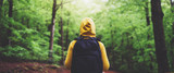 Fototapeta Na ścianę - tourist traveler with backpack standing into road at summer green forest, view back girl hiker in yellow hoody looking and enjoying the breath of fresh clean air in trip, relax holiday concept