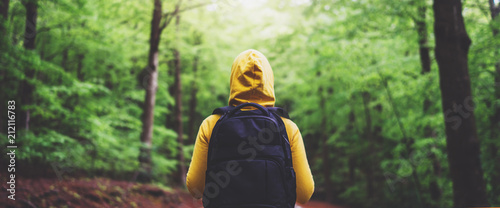 Fotografie, Obraz  tourist traveler with backpack standing into road at summer green forest, view b