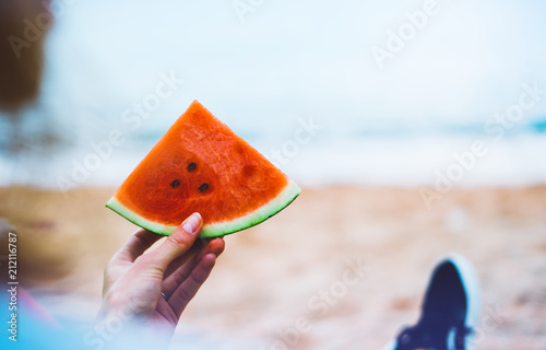 young girl hipster relax on beach coast and holds in her hand a slice of red fresh fruit watermelon on blue sea background, woman on seaside nature eating food, vacation in summer concept
