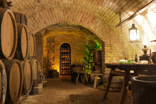 Tuinposter Oude gebouw Vintage wine cellar interiors: stack of oak barrels, wooden old-style furniture with glass instruments and rack with dust covered wine bottles