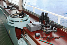 Marine Navigation Instruments On The Bridge Of Ship At Sea: Sextant, Chronometer, Navigation Map And Binoculars
